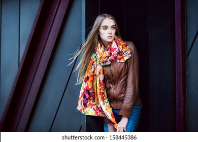 Beautiful fashion woman wearing leather coat and scarf posing against modern wall