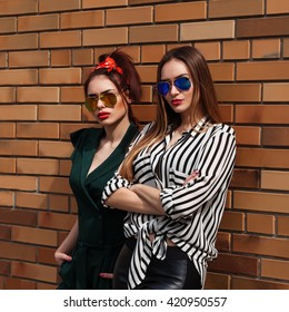 Beautiful fashion women posing. Trendy lifestyle urban portrait on city background. Girls wearing in style clothes and accessories