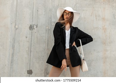 Beautiful fashion young woman with bag in summer vintage white hat in trendy black blazer in sexy top in elegant glasses stands near gray wall on street. Casual business outfit.