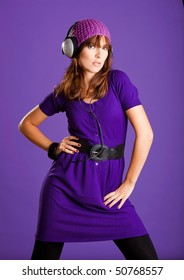 Beautiful fashion young woman listen music with headphones, over a violet background