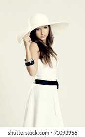 Beautiful and fashion young woman posing and wearing a wonderful white dress with a white hat