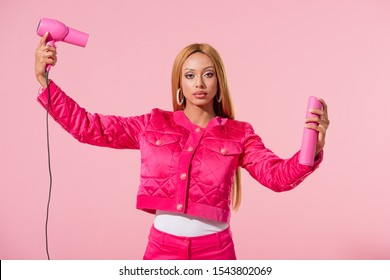 beautiful, fashionable african american woman holding hair spray and hairdryer isolated on pink, fashion doll concept