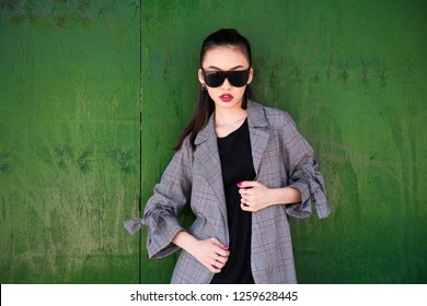 Beautiful fashionable Asian girl wearing casual outfit and sunglasses posing against green wooden wall