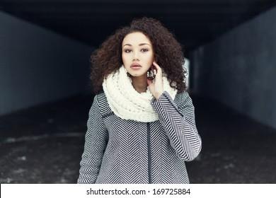 Beautiful fashionable black girl posing in a winter coat