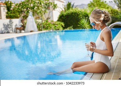 Beautiful fashionable blonde girl in swimsuit with glass of champagne is posing in swimming pool outdoors