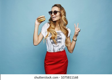 Beautiful and fashionable blonde model girl with charming smile, in red skirt white t-shirt and sunglasses, with hamburger in her hand have a fun and posing at blue background in studio