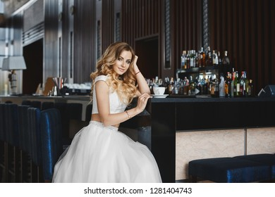 Beautiful and fashionable blonde model girl with perfect body and with bright makeup in the stylish skirt and in trendy t-shirt sits at the bar with a cup of coffee and posing at a cafe