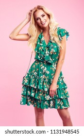 Beautiful fashionable blonde woman in nice green dress with flowers, handbag and sunglasses. Fashion spring summer photo.