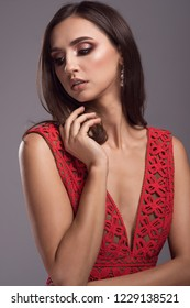 Beautiful fashionable brunette woman in elegant red dress, handbag and accessories. Fashion spring summer autumn photo. Jewelry. Red carpet look
