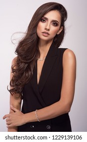 Beautiful fashionable brunette woman in elegant black dress, handbag and accessories. Fashion spring summer autumn photo. Jewelry.