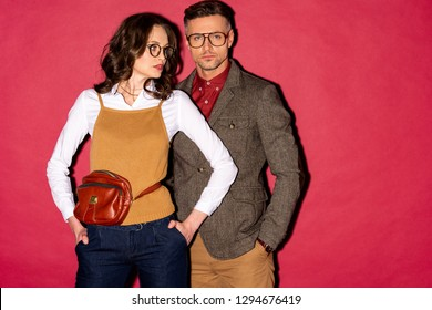 beautiful fashionable couple in formal wear and glasses posing on red background