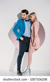 beautiful fashionable couple in love looking away while standing together in hole on grey