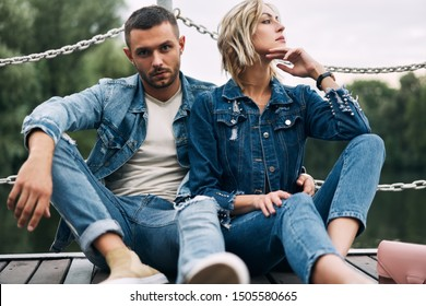 Beautiful fashionable couple posing on river bridge wearing denim jeans.  Fashion people, love, emotions and relationship concept