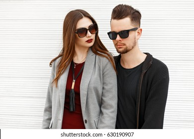 Beautiful fashionable couple in sunglasses near white wooden wall