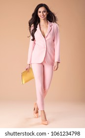 Beautiful fashionable elegant woman well dressed, handbag and accessories. Fashion spring summer photo. Pink suit