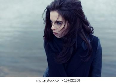 Beautiful fashionable girl in autumn coat near the water