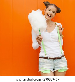 Beautiful fashionable girl with candy-floss posing next to the orange wall. Outdoor. Warm colors