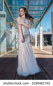Beautiful, fashionable girl in dress in front of modern building