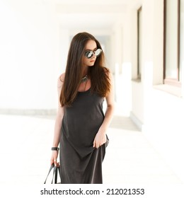 Beautiful fashionable girl with glasses and a dress is on a sunny day