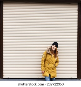 Beautiful fashionable girl in a jacket and hat in autumn on a background of a wall
