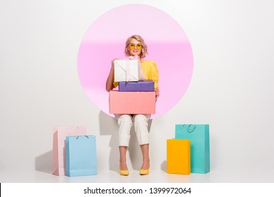 beautiful fashionable girl posing with colorful gift boxes and shopping bags on white with pink circle