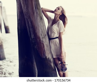 Beautiful fashionable girl standing near the pier in water in a dress with shoes in hand
