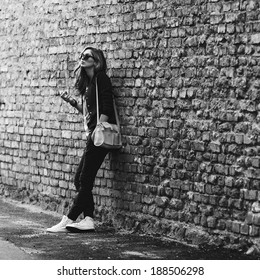 Beautiful fashionable girl stands near the brick wall with a cigarette , black and white