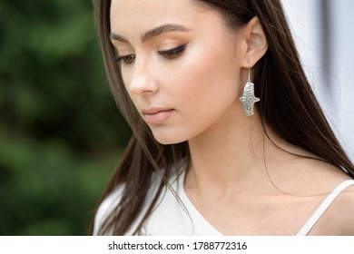 beautiful fashionable girl in stylish jewelry. The model poses in the street with flowering trees. Spring