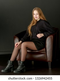 Beautiful, fashionable girl teenager studio photo on a black background. The concept of style and fashion layout for the magazine.
