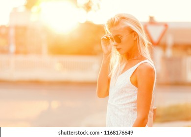Beautiful fashionable hipster model woman with sunglasses in a trendy white dress on the street at sunset