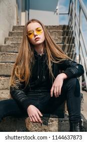 beautiful fashionable kid girl with long hair in yellow sunglasses in city, Street fashion kid,