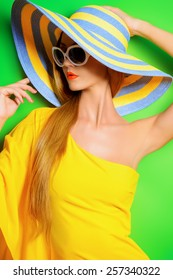 Beautiful fashionable lady wearing bright yellow dress over green background. Beauty, fashion concept. Optics. Summer vacation.