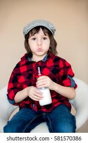 Beautiful fashionable little preschool boy, drinking milk from bottle, isolated image