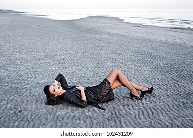 Beautiful fashionable model on the beach in beautiful dress