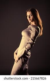 Beautiful fashionable model posing at studio in elegant long dress.