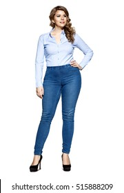 Beautiful fashionable plump woman in jeans and a denim shirt standing on a white background