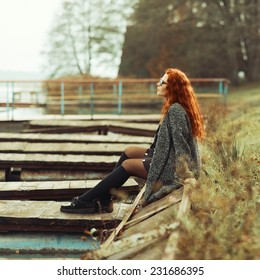Beautiful fashionable red-haired girl sitting resting near the lake