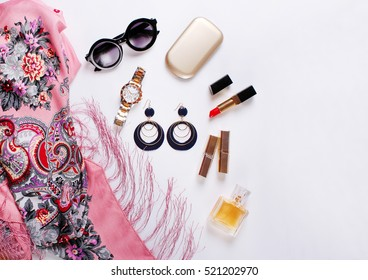 beautiful fashionable scarf, sunglasses, perfume, earrings on a white background