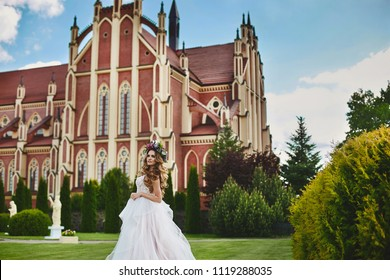 Beautiful fashionable and sexy blonde model girl in wedding white dress with floral wreath on her head posing in front of gothic church