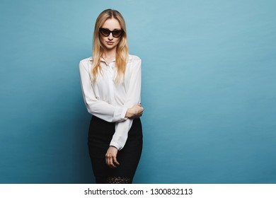 Beautiful, fashionable and sexy blonde model girl in stylish sunglasses and in a white blouse and black tight skirt posing at the blue background in a studio, isolated