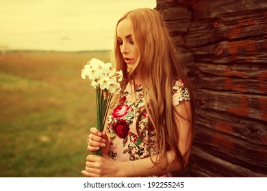 Beautiful fashionable sexy cute girl leaning against the house stands with flowers