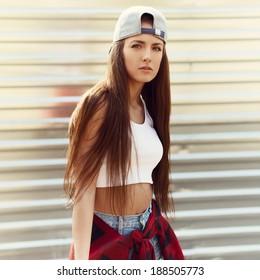 beautiful fashionable sexy girl standing near a metal wall