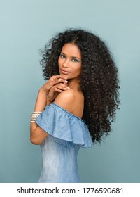 Beautiful fashionable slender young woman from Santo Domingo with long curly black hair wearing subtle makeup posing sideways looking at the camera against a blue studio background