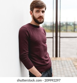 Beautiful fashionable stylish man with a beard standing near the wall
