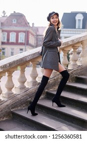 beautiful fashionable stylish woman in gray coat and black knee high heel boots walking and posing outdoors, , street style shooting
