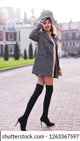 beautiful fashionable stylish woman in gray coat and black knee high heel boots walking and posing outdoors, street style shooting
