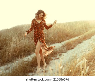 Beautiful fashionable woman in a dress in the sun in the wind walks in a field on the way