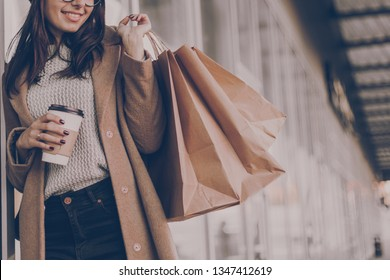 Beautiful fashionable woman drink coffee walking near mall with shopping bags.