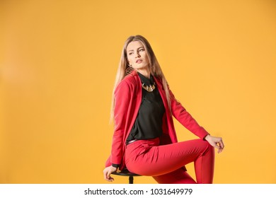 Beautiful fashionable woman in elegant suit on color background