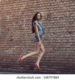 Beautiful fashionable woman in a jump near the brick wall